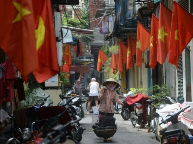 A street vendor walks past rows of Vietnamese national flags hung in outside homes in downtown Hanoi