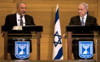 Israeli Prime Minister Benjamin Netanyahu (R) and Defence Minister Avigdor Lieberman speak at the Knesset in Jerusalem
