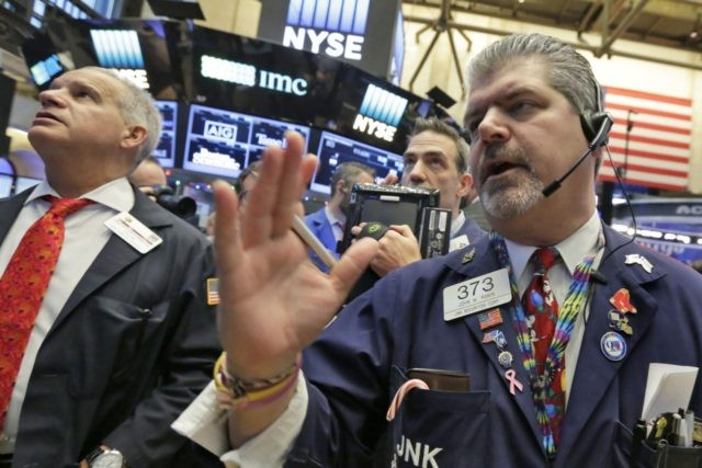 Trader John Panin, right, works on the floor of the New York Stock Exchange, Wednesday, Dec. 14, 2016. Stocks are little changed on Wall Street in early trading, a day after indexes set their latest all-time highs. (AP Photo/Richard Drew)