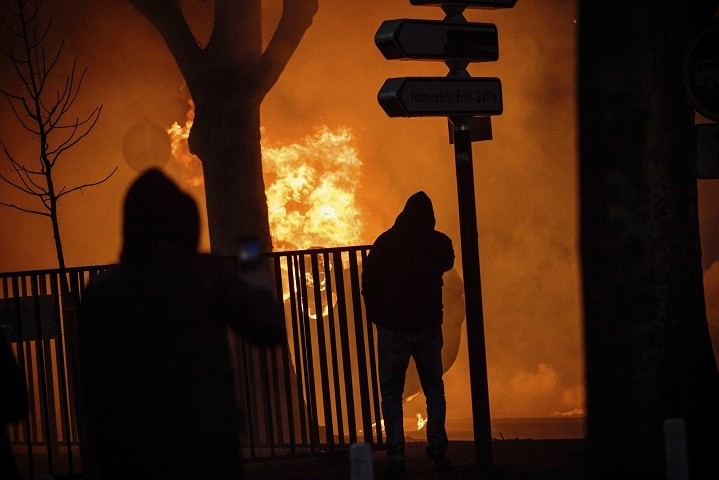 Protestors watch a car burning after a demonstration in Bobigny outside Paris, Saturday, Feb. 11, 2017. A peaceful demonstration protesting the alleged rape of a black youth by police has degenerated, with small groups setting at least one vehicle afire and throwing projectiles at police. (AP Photo/Aurelien Morissard)
