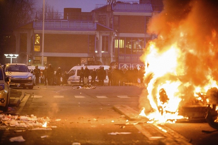 French police officers face protestors as a car burns in Bobigny, outside Paris, Saturday, Feb. 11, 2017. A peaceful demonstration protesting the alleged rape of a black youth by police has degenerated, with small groups setting at least one vehicle afire and throwing projectiles at police. (AP Photo/Aurelien Morissard)