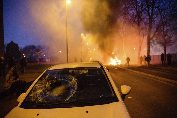 Protestors walk past a burning car after a demonstration in Bobigny outside Paris, Saturday, Feb. 11, 2017. A peaceful demonstration protesting the alleged rape of a black youth by police has degenerated, with small groups setting at least one vehicle afire and throwing projectiles at police. (AP Photo/Aurelien Morissard)