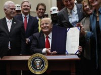 President Donald Trump smiles after signing H.J. Res. 38 in the Roosevelt Room of the White House in Washington, Thursday, Feb. 16, 2017. The president is surrounded by coal miners and members of congress including from left, Rep. Bill Johnson, R-Ohio, Rep. Jim Renacci, R-Ohio, Sen. Joe Manchin, D-W.Va., Sen. Heidi Heitkamp, D-N.D., and Sen. Shelley Moore Capito, R-W.Va. (AP Photo/Carolyn Kaster)