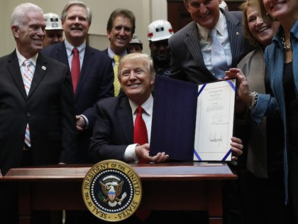 President Donald Trump smiles after signing H.J. Res. 38 in the Roosevelt Room of the White House in Washington, Thursday, Feb. 16, 2017. The president is surrounded by coal miners and members of congress including from left, Rep. Bill Johnson, R-Ohio, Rep. Jim Renacci, R-Ohio, Sen. Joe Manchin, D-W.Va., Sen. …