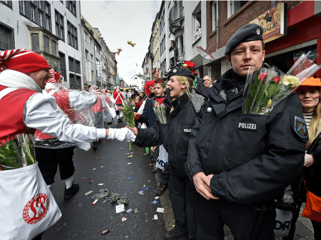 Police get flowers by revelers while they secure the traditional carnival parade in Cologne, western Germany, Monday, Feb. 8, 2016. Many carnival parades in Germany were cancelled because of stormy weather. The foolish street spectacle in Cologne, normally watched by hundreds of thousands of people, is the highlight in Germany's …