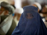 An Afghan women covered with a burqa listens to the former Taliban commander and presidential candidate Mullah Abdul Salam Rocketi's speech, during a campaign rally in Kabul, Afghanistan, Friday, Aug. 14, 2009. Afghans will head to the polls on Aug. 20 to elect a new president. (AP Photo/Farzana Wahidy)