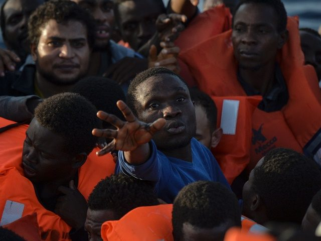 TOPSHOT - Migrants and refugees seated on a rubber boat grab life jackets thrown by members of the crew of the Topaz Responder rescue ship run by Maltese NGO Moas and Italian Red Cross, off the Libyan coast in the Mediterranean Sea, on November 3, 2016. / AFP / ANDREAS …