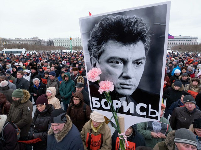 FILE - In this Sunday, Feb. 26, 2017 file photo, People gather in memory of opposition leader Boris Nemtsov, portrait in center, in St. Petersburg, Russia. Russia's opposition movement struggles to rally around one unifying figure two years after Nemtsov, a former deputy prime minister, was gunned down just outside the Kremlin wall. (AP Photo/Dmitri Lovetsky, file)