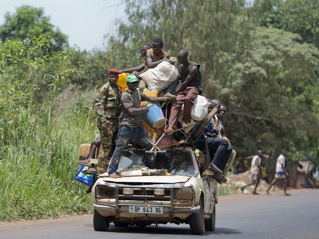 People stand on a car with their belongings on the road from Mbaiki to Bangui on April 8, 2014. The crisis in the strife-torn Central African Republic has left 1.6 million people -- a third of the population -- in urgent need of food, the United Nations said Monday. Thousands of people have been killed in a wave of sectarian violence across the Central African Republic that has lasted for more than a year, despite the presence of African Union and French peacekeeping troops. AFP PHOTO / MIGUEL MEDINA        (Photo credit should read MIGUEL MEDINA/AFP/Getty Images)