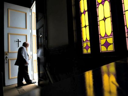 A parishioner at First Baptist Church, a predominantly African-American congregation, leaves after a worship service in Macon, Ga., on Sunday, July 10, 2016. There are two First Baptist Churches in Macon _ one black and one white. (AP Photo/Branden Camp)