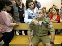 Israeli solider, Sgt. Elor Azaria, sits inside an Israeli military court in Tel Aviv, Israel, Monday, April 18, 2016. An Israeli military court charged Azaria with manslaughter for the fatal shooting of a wounded Palestinian attacker in the West Banks. The shooting in the city of Hebron was caught on tape and showed the Palestinian attacker lying on the ground and raising his head before a soldier shoots him in the head. The incident has deeply divided the nation.  (AP Photo/Ariel Schalit)