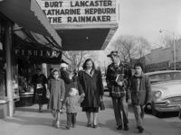 1957: Hungarian refugee Bela Feher with his wife Lucy and their three children Vera, Cseve and Michael, walking along Main Street in Patchogue, Long Island, their new home. The film 'The Rainmaker', starring Katharine Hepburn and Burt Lancaster, is showing at the local cinema. (Photo by Vecchio/Three Lions/Getty Images)