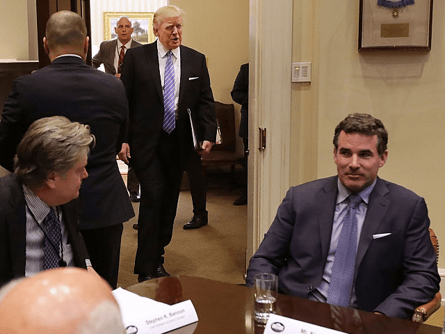 WASHINGTON, DC - JANUARY 23: U.S. President Donald Trump (C) walks into the Roosevelt Room for a meeting with Mark Sutton of International Paper, Jeff Fettig of Whirlpool, White House Senior Counselor Steve Bannon, Kevin Plank of Under Armour, Elon Musk of SpaceX (L) and other other business leaders at …