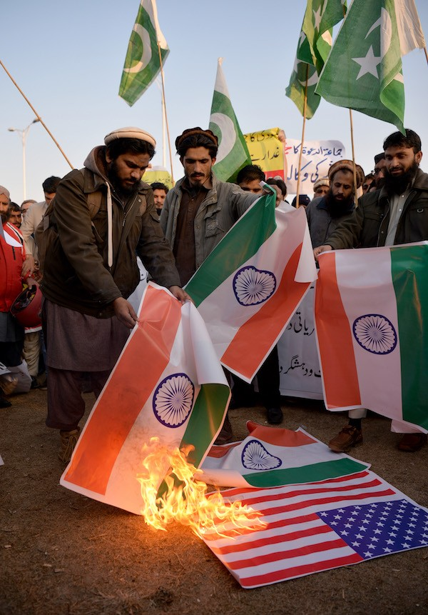 Pakistani supporters of the Jamaat-ud-Dawa (JuD) organisation burn Indian (R) and US flags after JuD leader, Hafiz Saeed was placed under house arrest by authorities in Islamabad on January 31, 2017. A Pakistani militant group held protests in the country's major cities after its leader, one of the alleged masterminds of the 2008 Mumbai attacks, was placed under house arrest following years of foreign pressure. / AFP / AAMIR QURESHI (Photo credit should read AAMIR QURESHI/AFP/Getty Images)