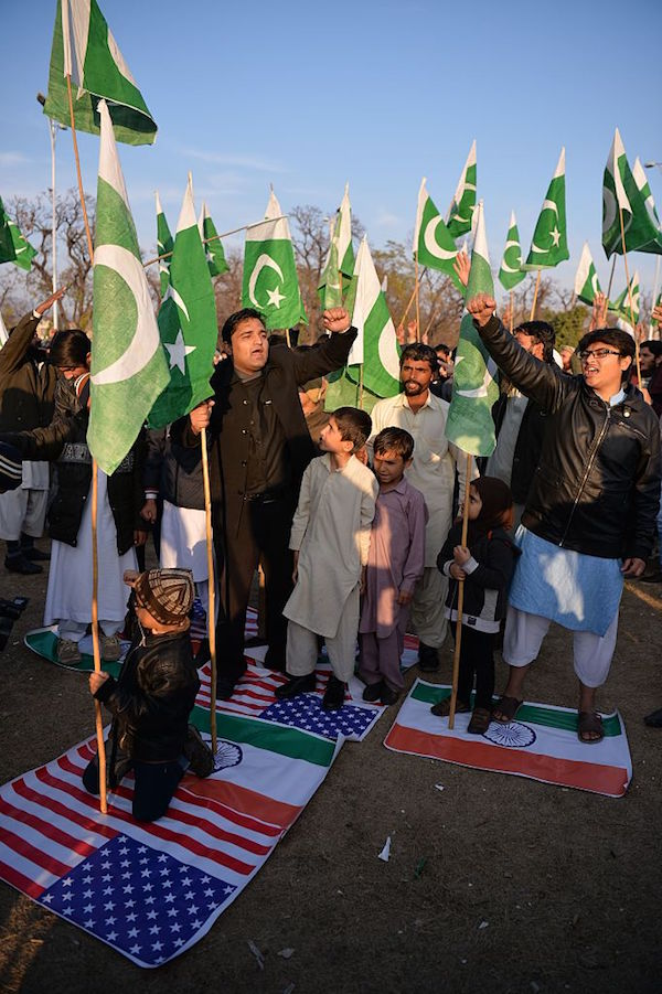 Pakistani supporters of the Jamaat-ud-Dawa (JuD) organisation stand on Indian (R) and US flags during a protest after JuD leader, Hafiz Saeed was placed under house arrest by authorities in Islamabad on January 31, 2017. A Pakistani militant group held protests in the country's major cities after its leader, one of the alleged masterminds of the 2008 Mumbai attacks, was placed under house arrest following years of foreign pressure. / AFP / Aamir QURESHI (Photo credit should read AAMIR QURESHI/AFP/Getty Images)
