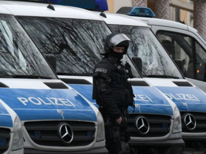 A policeman of a special unit stands next to police cars on the grounds of the Bilal mosque in the Griesheim district of Frankfurt am Main, western Germany, on February 1, 2017. German police arrested a Tunisian man suspected of recruiting for the Islamic State group and planning an attack, …