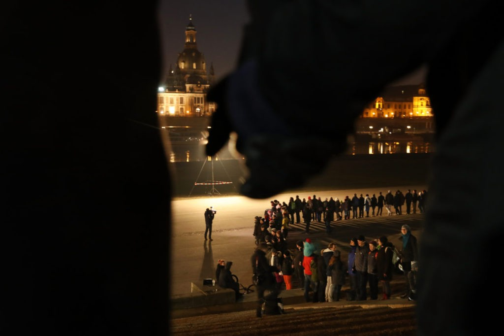 DRESDEN, GERMANY - FEBRUARY 13:  People hold hands to form a human chain across from the rebuilt, historic city center to both commemorate the 72nd anniversary of the Dresden firebombing and to make a statement against right-wing groups who seek to use the anniversary for political ends on February 13, 2017 in Dresden, Germany. In the February 13-14, 1945, attack on Dresden Allied bombers obliterated the city center in a carefully planned firestorm that killed at least 25,000 people only a few months before the end of World War II.  (Photo by Sean Gallup/Getty Images)