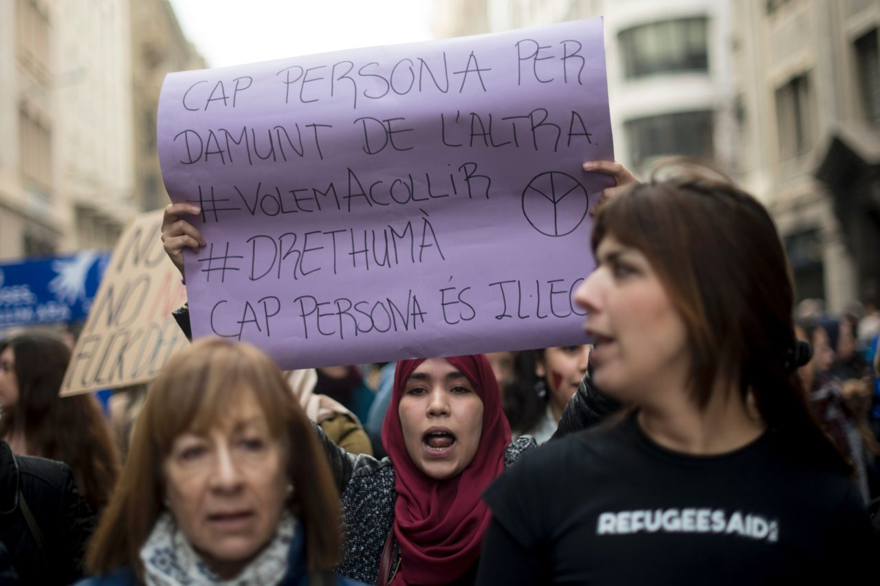 A woman holds a placard reading in Catalan 'No one is above another, No one is illegal' (JOSEP LAGO/AFP/Getty Images)