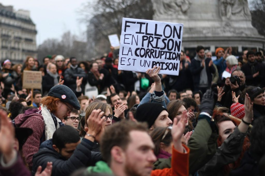 """A demonstrator holds a placard reading """"Fillon to prison, corruption is a poison"""" during a rally to protest against the corruption of the elected representatives in place de la Republique, in Paris, on February 19, 2017. / AFP / Lionel BONAVENTURE        (Photo credit should read LIONEL BONAVENTURE/AFP/Getty Images)"""