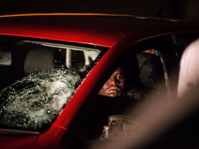 A man sits in his damaged car after it was smashed by residents of the worker's hostel in Jeppe's Town neighbourhood of Johannesburg on February 26, 2017. Violence flared up again around the restive hostels of Jeppe's Town, theatre of violence during the xenophobic violence of 2015. Shops and homes …