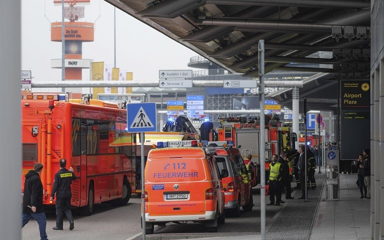 Ambulances stand outside the Hamburg, northern Germany, airport Sunday, Feb. 12, 2017 after several people were injured by an unknown toxic that likely spread through the airports' air conditioning system. (Axel Heimken/dpa via AP)