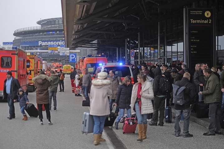Travellers wait outside the Hamburg, northern Germany, airport Sunday, Feb. 12, 2017 after after several people were injured by an unknown toxic that likely spread through the airports' air conditioning system. (Axel Heimken/dpa via AP)