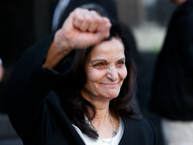 Rasmea Odeh raises her fist as she leaves federal court in Detroit Thursday, March 12, 2015. A judge sentenced the Chicago activist to 18 months in federal prison Thursday for failing to disclose her convictions for bombings in Israel when she applied to be a U.S. citizen. Odeh, 67, also …