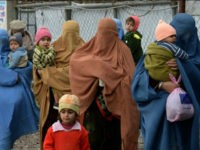 Afghan refugee women carry their children as they arrive to update their family data at the UNHCR Verification Center in Chamkani, on the outskirts of Peshawar on January 26, 2017. More than 380,000 registered Afghan refugees returned from Pakistan in 2016. / AFP / ABDUL MAJEED (Photo credit should read …