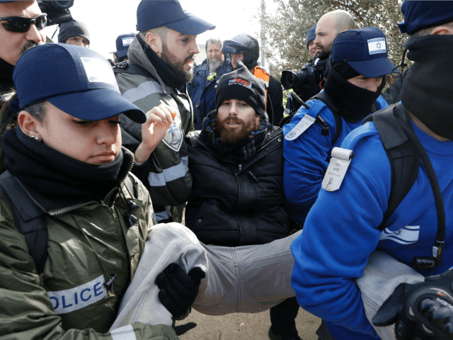 Israeli security forces carry a settler from the Amona outpost, northeast of Ramallah, on February 1, 2017 as they evict the hardline occupants of the wildcat settlement outpost in line with a High Court ruling that determined the homes were built on private Palestinian land. Israeli police began evicting dozens …