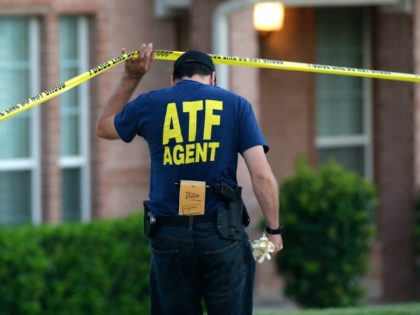 An ATF agent lifts crime scene tape outside the scene of two murders Thursday morning, Aug. 8, 2013, in DeSoto, Texas. Four people were killed at two different locations in South Dallas County and the suspected shooter is in police custody. (AP Photo/LM Otero)