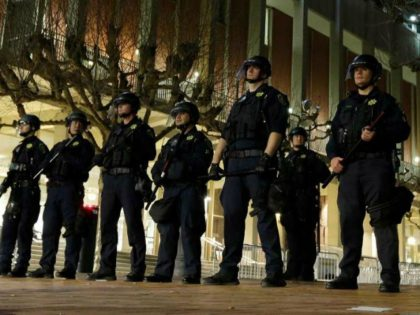 University of California at Berkeley police guard the building where Breitbart News editor Milo Yiannopoulos was to speak Wednesday, Feb. 1, 2017, in Berkeley, Calif. A small group of people with their faces covered broke windows, hurled fireworks at police officers and threw smoke bombs, prompting UC Berkeley officials to …