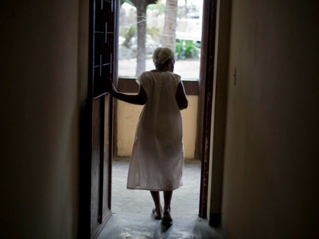 An elderly woman walks in a corridor at the Asile Commune home for the elderly in the Bel-Air slum of Port-au-Prince, Haiti, Friday Feb. 18, 2011. Things were supposed to be getting better at Asile Commune after the Jan. 2010 earthquake when British-based HelpAge assumed day-to-day management of the nursing …