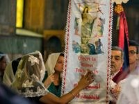 Coptic Christian touch a flag with an image of Jesus Christ during prayes for the departed remembering the victims of EgyptAir flight 804 at Al-Boutrossiya Church, the main Coptic Cathedral complex, in Cairo, Egypt, Sunday, May 22, 2016. The Airbus A320 plane was flying from Paris to Cairo with 66 passengers and crew when it disappeared early last Thursday over the Mediterranean Sea. (AP Photo/Amr Nabil)