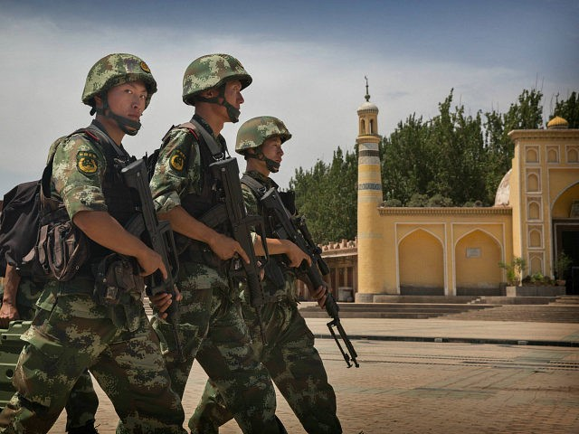 KASHGAR, CHINA - JULY 31: Chinese soldiers march in front of the Id Kah Mosque, China's largest, on July 31, 2014 in Kashgar, China. China has increased security in many parts of the restive Xinjiang Uyghur Autonomous Region following some of the worst violence in months in the Uyghur dominated area. (Photo by Getty Images)