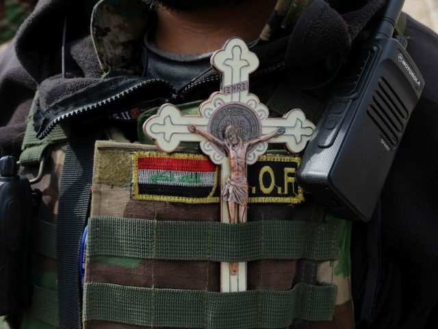 Rami Raad, a fighter with Shiite Popular Mobilization Forces, placing a cross and Iraqi flag on his uniform as he stands guard in recently liberated from Islamic State and predominantly Christian town of Tilkaif, Iraq, Saturday, Jan. 21, 2017. (AP Photo/Khalid Mohammed)