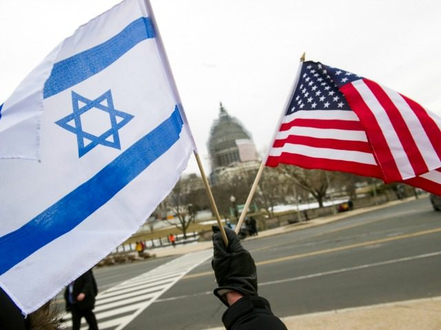 """A pro-Israel demonstrators waves flags, toward the Capitol in Washington, Tuesday, March 3, 2015, as Israeli Prime Minister Benjamin Netanyahu addressed a joint meeting of Congress. In a speech that stirred political intrigue in two countries, Netanyahu told Congress that negotiations underway between Iran and the U.S. would """"all but …"""