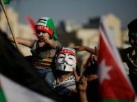 """A man wears a Guy Fawkes mask and carries his daughter during a celebration by the Muslim Brotherhood movement to declare victory of Gaza and Hamas against Israel, in Amman, Jordan, Friday, Aug. 29, 2014. Thousands of followers and supporters of the Muslim Brotherhood movement in Jordan celebrate what they call """" Hamas' Victory"""" against Israel. (AP Photo/Mohammad Hannon)"""