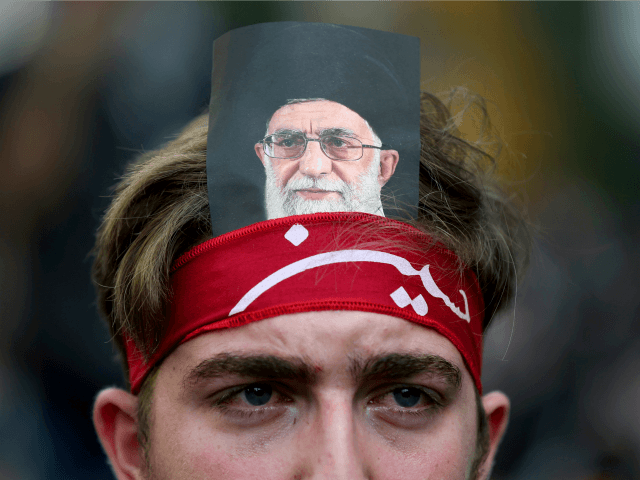 A Lebanese Shiite supporter of the Iranian-backed Hezbollah group, with a portrait on his head of Iran's supreme leader Ayatollah Ali Khamenei, weeps as he listens to the death story of Imam Hussein during the holy day of Ashoura, in a southern suburb of Beirut, Lebanon, Wednesday, Oct. 12, 2016. Lebanese Shiites mark Ashoura, the tenth day of the Islamic month of Muharram, to commemorate the Battle of Karbala in the 7th century when Imam Hussein, a grandson of Prophet Muhammad, was killed in present-day Iraq. (AP Photo/Hussein Malla)