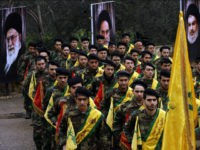 Lebanese Hezbollah fighters march near portraits of Iran's Supreme Leader Ayatollah Ali Khamenei (L), founder of Iran's Islamic Republic, late Ayatollah Ruhollah Khomeini and Hezbollah leader Hassan Nasrallah, during a parade on February 14, 2015 in the southern Lebanese town of Jibsheet. The Lebanese Shiite movement Hezbollah is marking today …