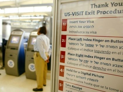 A sign outlines the procedure on how to use the US-VISIT as Carmen Moreno (L) and Joan Walker (C), employees of the U.S. Department of Homeland Security, stand by the newly installed kiosks which scans passports and fingerprints, a biometric procedure that is required of all foreigners exiting Newark Liberty …