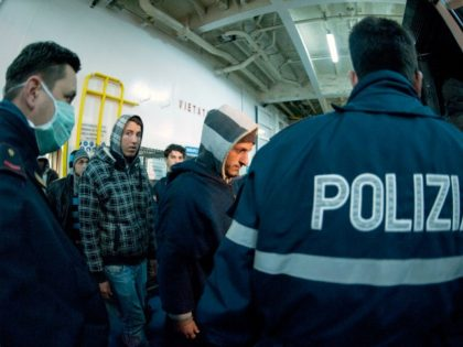 Italian Police escort would-be migrants believed to be from North Africa as they are disembarked off a ferry boat in the Sicilian port of Porto Empedocle, Italy, early Sunday, Feb. 13, 2011 after their boat reached the island of Lampedusa from North Africa. Italy has ferried hundreds of Tunisians off …