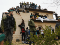 Israeli security forces stand guard as youths supporters of settlements sit on the rooftop of a house which is due to be emptied and demolished in the settlement of Ofra in the occupied West Bank, during an operation by Israeli forces to evict the houses, on February 28, 2017. Nine …