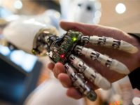 A visitor holds a hand of AILA, or Artificial Intelligence Lightweight Android, during a demonstration at the German Research Center for Artificial Intelligence GmbH (Deutsches Forschungszentrum fuer Kuenstliche Intelligenz GmbH) stand at the 2013 CeBIT technology trade fair on March 5, 2013 in Hanover, Germany. CeBIT will be open March …