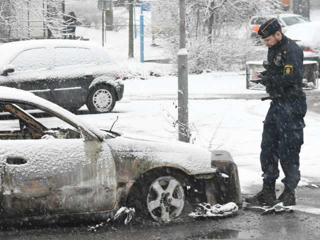 A policeman investigates a burned out car in the suburb Rinkeby, outside Stockholm, on February 21, 2017. Several cars was set in to fire after a riot in Rinkeby. The turmoil started when the police was going to arrest a man in the area. They where attacked with stones and …