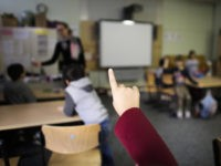 In this Tuesday, Oct. 6, 2015 photo a child rises her hand to answer a question of teacher Sandra Wiandt, background, at a so-called Willkommensklasse (Welcome Class) at the elementary school at the Baeke in Berlin, Germany. As a new school year began last month, Berlin's schools saw non-German speaking children jump by 70 percent. There are now 478 welcome classes in the capital alone for roughly 5,000 new refugee children. (AP Photo/Markus Schreiber)