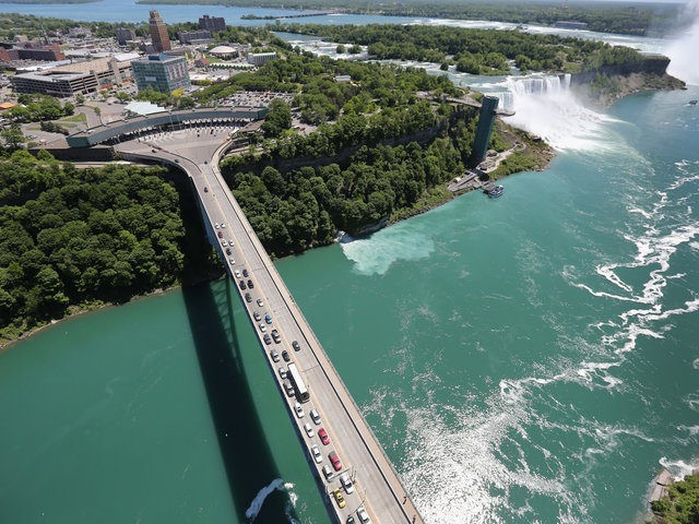 NIAGARA FALLS, NY - JUNE 04: The Rainbow Bridge crosses from the United States (L), into Canada near the Niagara Falls on June 4, 2013 at Niagara Falls, New York. The falls, which have a combined highest flow rate of any waterfall in the world, straddle the U.S.-Canada border, on …