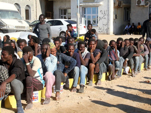 Illegal migrants sit in a port in Tagiura, east of the Libyan capital Tripoli, after 137 migrants of African origins were rescued by coast guard boats off the coast of Libya on July 21, 2016. / AFP / STRINGER (Photo credit should read STRINGER/AFP/Getty Images)