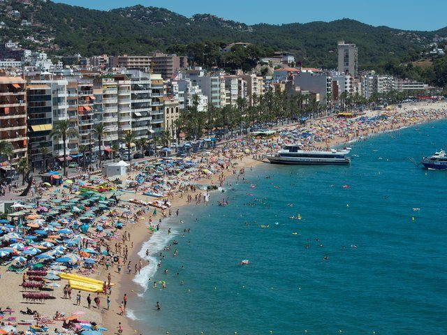 People enjoy the sea and beach in the Catalonian coastal city of Lloret de Mar, along the Mediterranean sea on August 7, 2016. / AFP / JOSEP LAGO (Photo credit should read JOSEP LAGO/AFP/Getty Images)