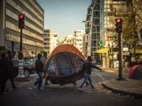 """TOPSHOT - Migrants carry a tent across a migrant tent camp in Paris on November 3, 2016, near to the Stalingrad metro station, one of several camps sprouting up around the French capital. Less than 300 kilometres from the recently-demolished """"Jungle"""" migrant camp in Calais, around 2,000 migrants are living …"""