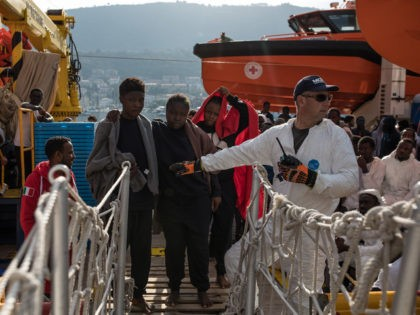 """VIBO VALENTIA, ITALY - NOVEMBER 24: Refugees wait to disembark the MOAS vessel """"Topaz Responder"""" on November 24, 2016 in Vibo Valentia, Italy. The MOAS team worked through the night of the 21st and into the next morning rescuing 'approximately' 600 people from several vessels though that figure could change. …"""